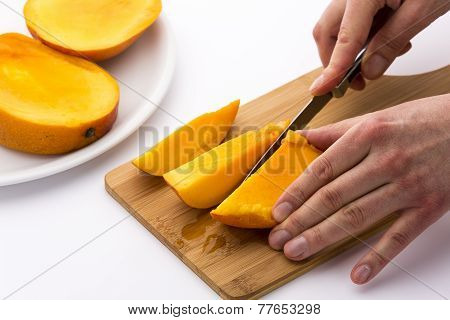 Mango Divided Into Thirds Being Subdivided Further