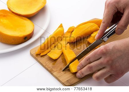 Two Hands Dicing A Mango Wedge With A First Cut