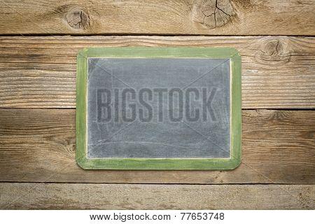 blank slate blackboard against rustic weathered wood planks