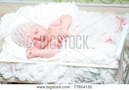 beautiful newborn baby boy sleeps in a small bed in white knitted cap