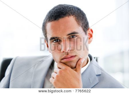 Portrait Of A Pensive Latin Businessman Sitting At His Desk