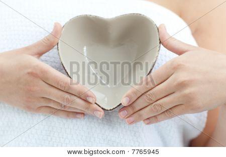 Primer plano de una mujer que sostiene un tazón en forma de un corazón