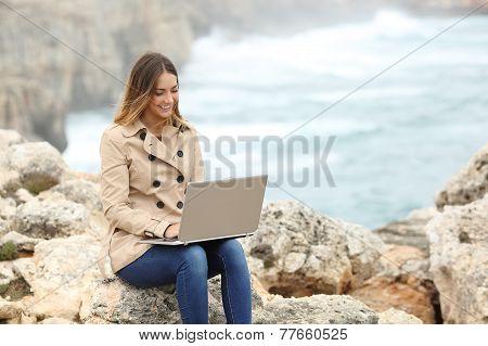 Beautiful Woman Browsing Her Laptop In Winter On The Coast