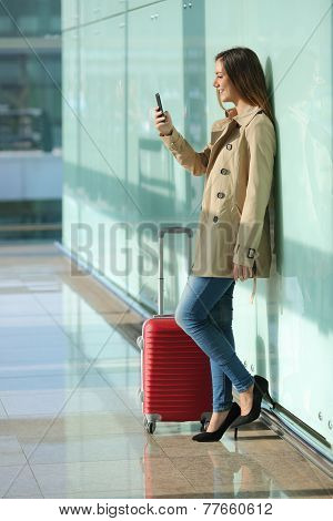 Traveler Woman Using A Smart Phone And Waiting In An Airport