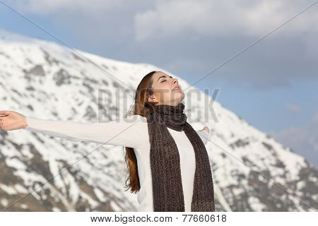 Woman Breathing Fresh Air Raising Arms In Winter