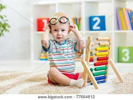 kid with eyeglasses playing abacus