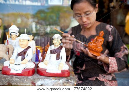 YANGON, MYANMAR - JANUARY 29 : Lady painting  statue of Buddha for souvenirs for tourist,  Jan 29, 2010, Myanmar. Small craft shops line the outter border of the Shwedagon temple in central Yangon.