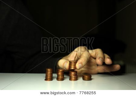 Male Hands Stacking Money To Piles