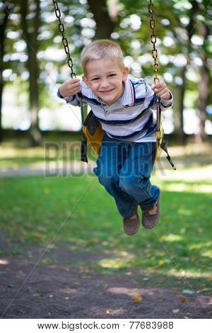 Smiling Little Blond Boy Swinging