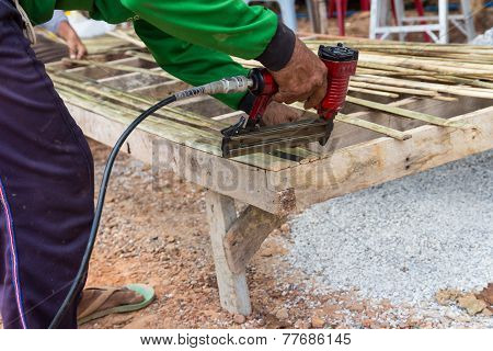 The Worker Use The Drill To Assemble The Wooden Seat