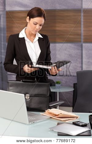 Young businesswoman arriving at office, looking at daily tasks in organizer.