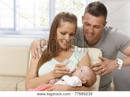 Happy mother feeding and caressing newborn baby, father hugging them.