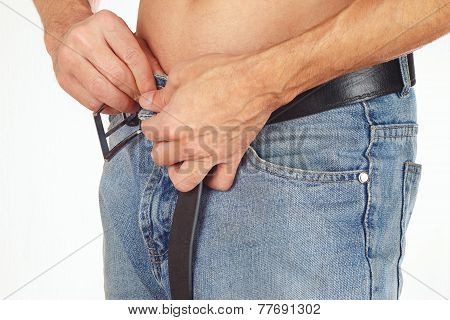Hands a shirtless guy buttons blue jeans closeup
