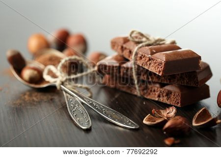 Tasty porous chocolate with nuts on table, close up