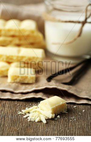 Tasty white porous chocolate with vanilla sticks and glass of milk, on wooden table