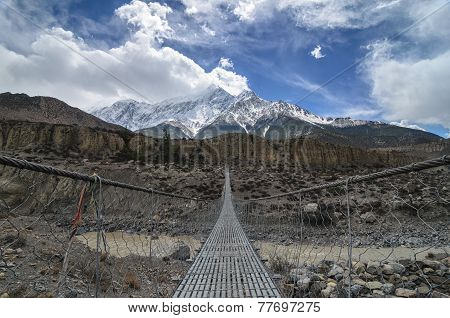Suspencion Bridge Across The Mountain River In Himalayas