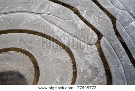 Concentric Curves Made In Ice Layer Over A Puddle