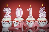 stock photo of red velvet cake  - Happy New Year for 2015 red velvet cupcakes in red and white theme with lit candles on a red background - JPG