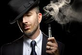 stock photo of e-cig  - male smoking a vapor cigarette as an alternative to tobacco - JPG