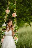 stock photo of swing  - A beautiful bride in a white wedding dress - JPG