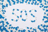 stock photo of sos  - sos word text made of blue tablets pills and capsules on white background - JPG