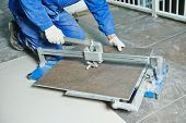 foto of overhauling  - industrial tiler builder worker working with floor tile cutting equipment at repair renovation work - JPG