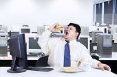 picture of junk food  - Young businessman with fat body working in the office while eating junk food - JPG