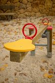 foto of seesaw  - Seesaw in a playground with scattered autumn leaves - JPG