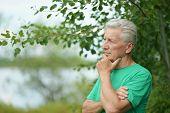 stock photo of mans-best-friend  - Serious senior man thinking in park on green background  - JPG