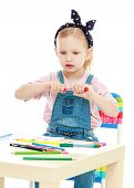 picture of montessori school  - Charming little girl draws with markers while sitting at table - JPG