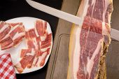 foto of shoulder-blade  - Knife cutting serrano ham slices with plate in the background - JPG