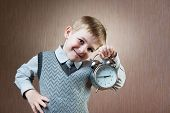 foto of diligent  - Portrait of cute diligent boy holding alarm clock - JPG