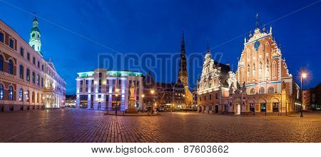 Famous House of Blackheads on the Town Square in Riga with a Church of St. Peter in the back. Latvia, after sunset.  House of Blackheads, destroyed during 2 World War, was reconstructed in the 1999.