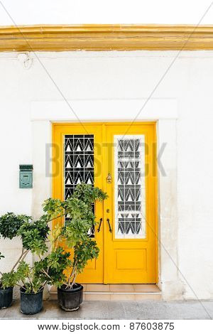 Wooden yellow door on the white building