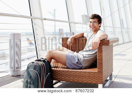 Happy young man in glasses and headphones sitting on chair in airport departure lounge