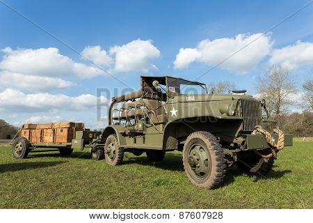 Military jeep vehicle pulling carriage with wooden boxes