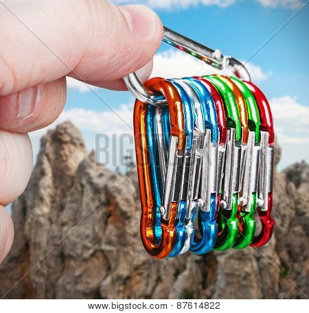 Colorful Carabiner Climbing In Hand On A Background Of Mountains