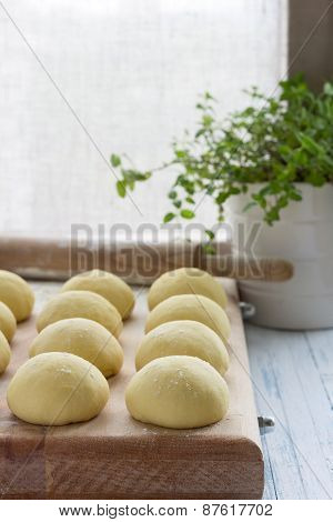Balls of fresh homemade dough on floured wooden board