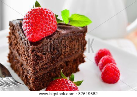 Fresh Home Made Sticky Chocolate Fudge Cake With Strawberries And Raspberries