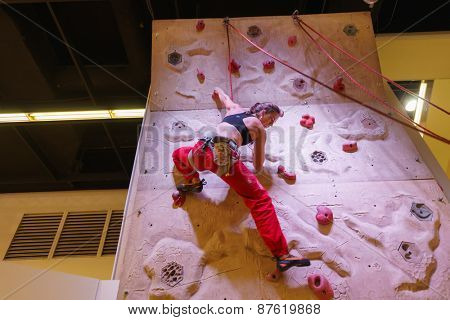 COLOGNE- SEP 19: woman climbing at the Photokina Exhibition on September 20, 2014 in Cologne, Germany. The Photokina is the world's largest trade fair for the photographic and imaging industries