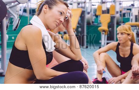 Woman tired with towel resting in the gym after training
