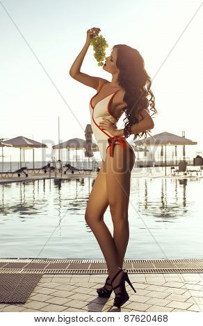 Sexy Woman With Dark Hair In Swimsuit Posing With Bunch Of Grapes
