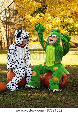 Playful boys in costumes sit on pumpkins