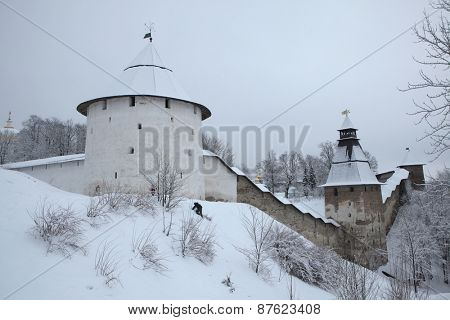 PECHORY, RUSSIA - JANUARY 22, 2011: Children sledge in front of the walls and towers of the Pskovo-Pechersky Monastery (Pskov Monastery of the Caves) near Pskov, Russia.