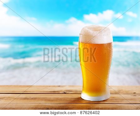 Glass Of Beer On Wooden Table Over Sea