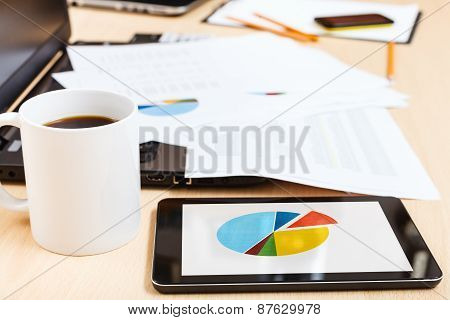 Mug Of Coffee And Tablet Pc With Chart On Desk