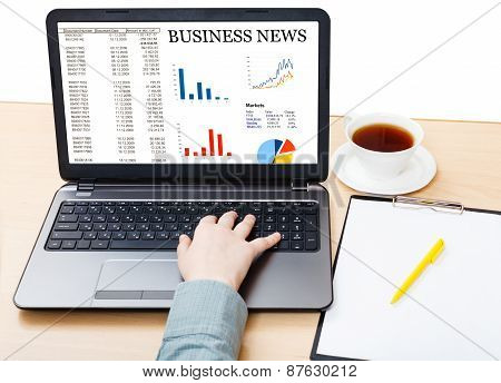 Laptop With Business News On Screen On Office Desk