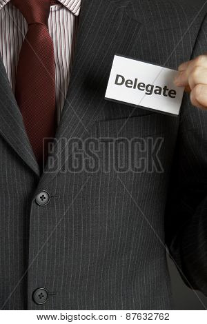 Businessman Attaching Delegate Badge To Jacket