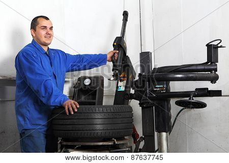 Auto Repairman Loading Automobile Car Wheel At Tyre Fitting Machine