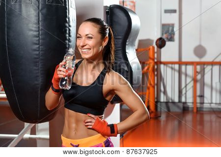 Female kickboxer drinks water